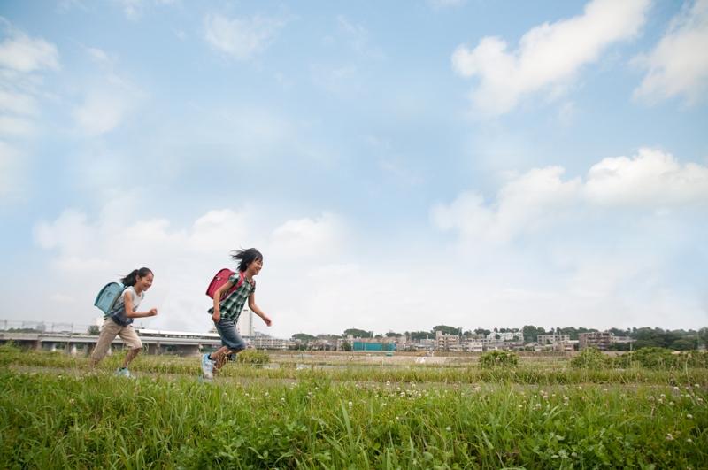 青い空の下でランドセルを背負って走っている子供