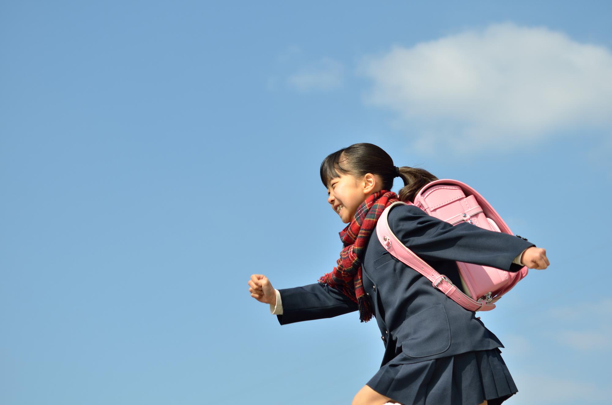 青い空の下でランドセルを背負って走っている女の子