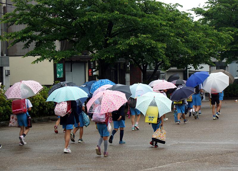 傘をさして歩く子どもたち